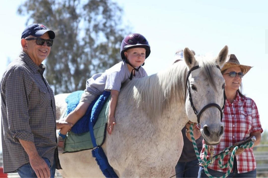 child-giving-horse-big-hug-from-saddle